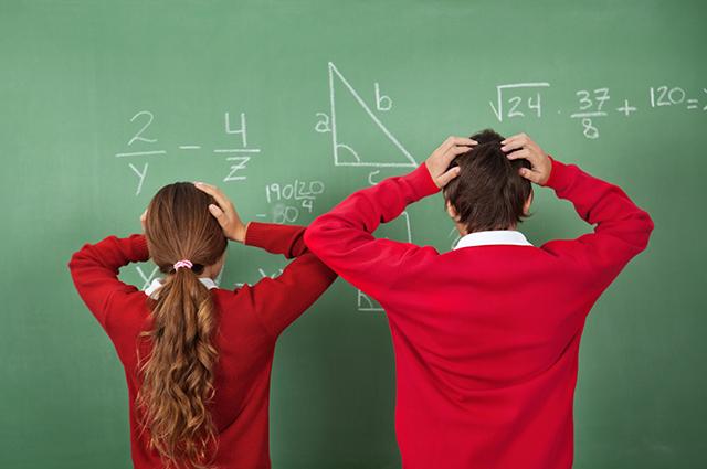 Dois alunos em frente a quadro negro