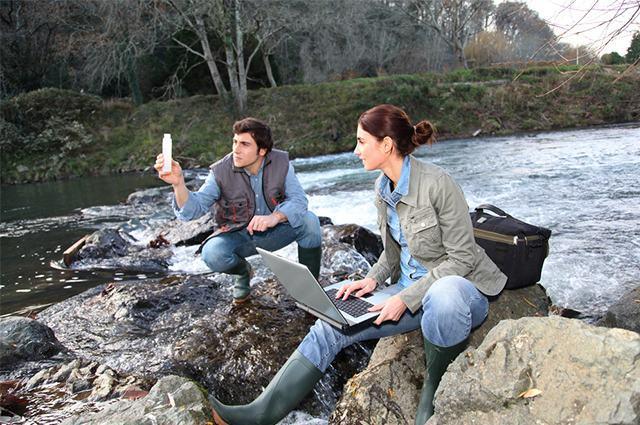 Biólogos em pedras próximo de rio