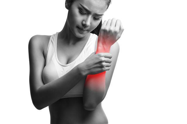 Mulher com mão em área afetada por dor muscular