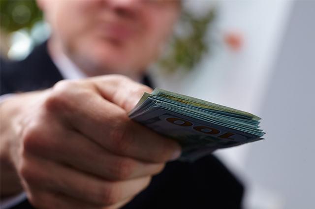 Mão segurando cédulas de dinheiro