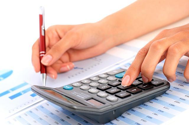 Mãos teclando em calculadora e segurando caneta