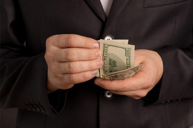 Imagem de homem de terno contando cédulas de dinheiro
