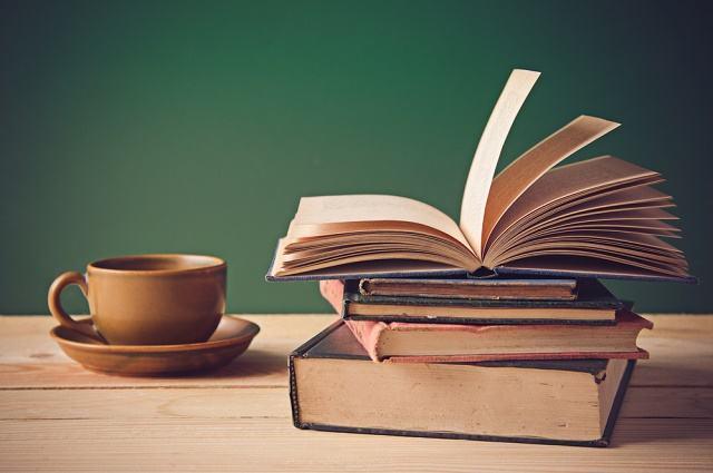 Imagem de livros e xícara em cima de mesa