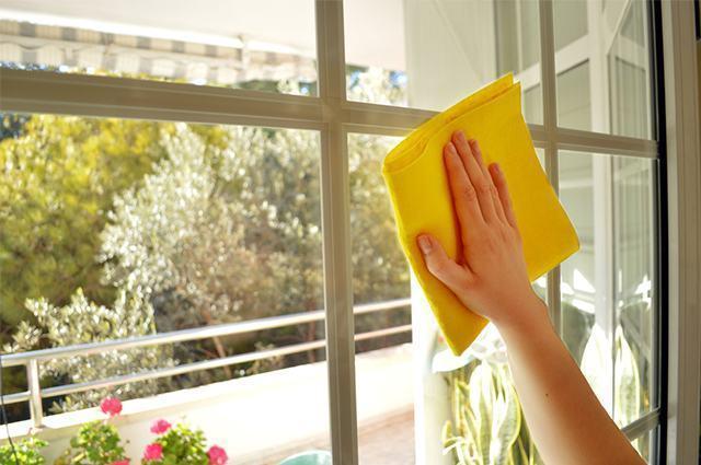 Imagem de mão limpando janela com pano
