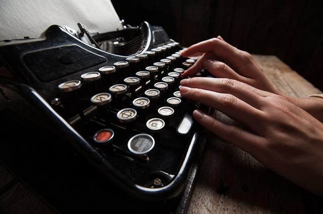 Imagem de mãos escrevendo em máquina de datilografia