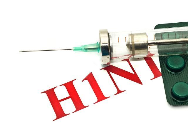 Imagem da sigla H1N1ao lado de comprimidos e seringa