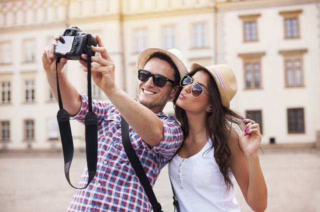 Imagem de casal de turistas tirando foto