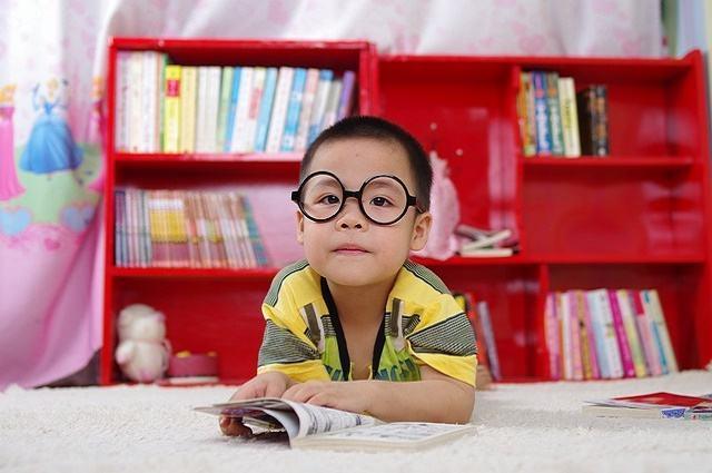 Imagem de garoto de óculos com livro aberto