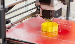 Detail of a 3D printer printing with a yellow ABS filament