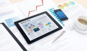 Modern business workplace with business news website on a digital tablet, mobile banking on a smartphone and some charts and graphs on a desktop.