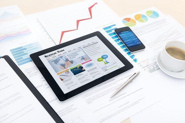 Imagem de tablet, celular e gráficos em textos
