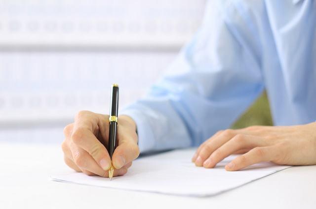 Imagem de mão escrevendo em papel