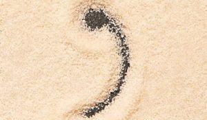 Comma symbol written on sand. Summer beach background