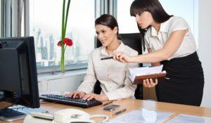 Two female business women in office setting working