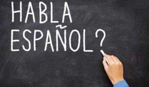 "Spanish language learning concept image. Teacher or student writing ""habla espanol"" on blackboard during spanish language course class."