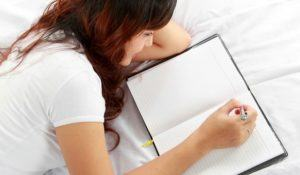 Closeup portrait of a relaxed young girl writing book while lying on the bed