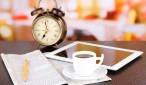 Tablet, newspaper, cup of coffee and alarm clock on wooden table