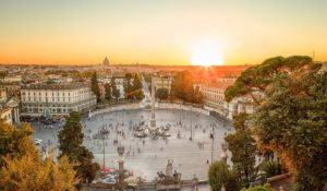 Aerial view of the large urban square, the Piazza del Popolo, Rome at sunset with the fiery orb of the sun dropping below the horizon above the rooftops of the historical buildings