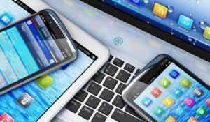 Mobility and modern telecommunication concept: macro view of tablet computer and touchscreen smartphones with colorful interfaces on laptop notebook PC