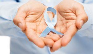 medicine, health care, gesture and people concept - close up of male hands holding blue prostate cancer awareness ribbon