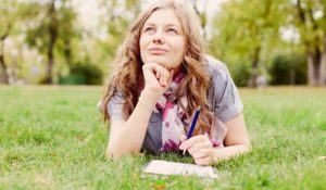 Teenage girl wearing checkered shirt and scarf lying down on grass in autumn park with notebook and pen in her hand and dreaming - inspiration concept
