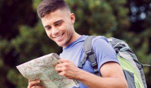 Traveling. Portrait of a young handsome tourist wearing blue t-short and backpack standing smiling and looking at the map in his hands