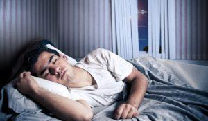 Man comfortably sleeping in his bed at night