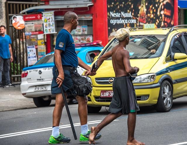 Rapaz negro sem camisa sendo algemado por policial na rua
