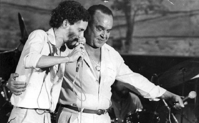 Foto em preto e branco de Luiz Gonzaga no palco ao lado de Gonzaguinha