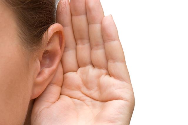 Mulher com mão na orelha