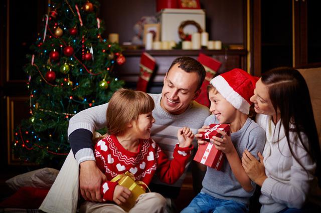 Família reunida próximo à árvore de natal segurando presentes