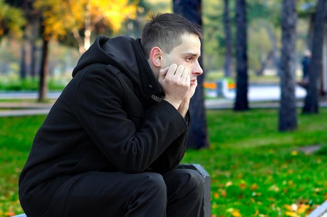 Homem sentado em praça chorando