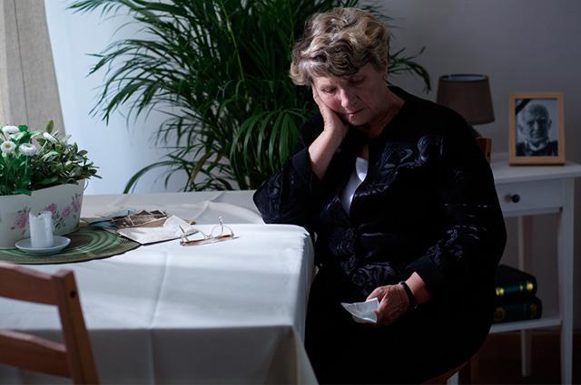 Senhora vestida de preto com o aspeto de tristeza