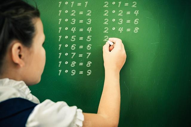 Menina escrevendo tabuada